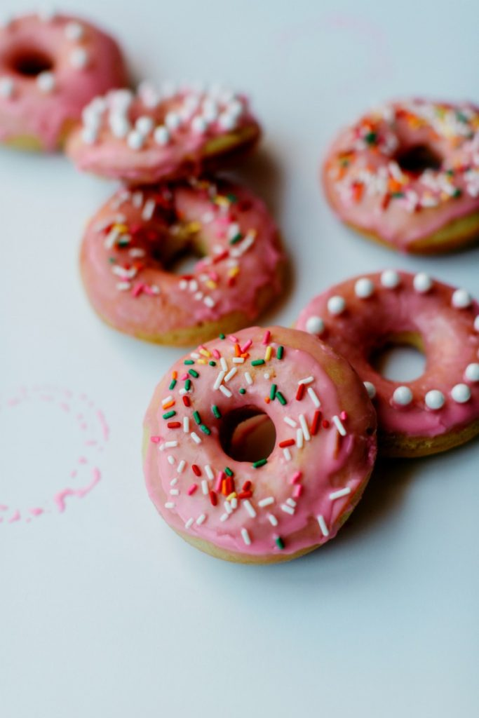 baked donuts with pink vanilla icing and sprinkles